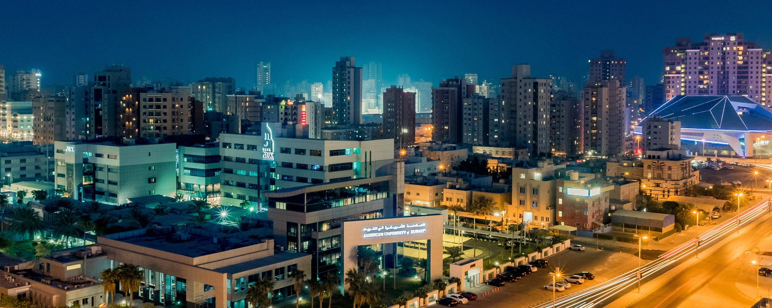 A night view of the American University of Kuwait and Kuwait City in the background.